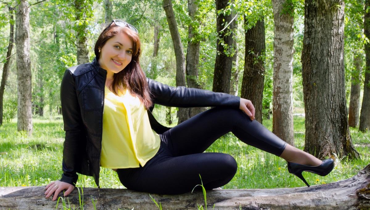 Alex in schwarzen Leggings, Higheels und gelber Bluse im Wald auf einem Baumstumpf